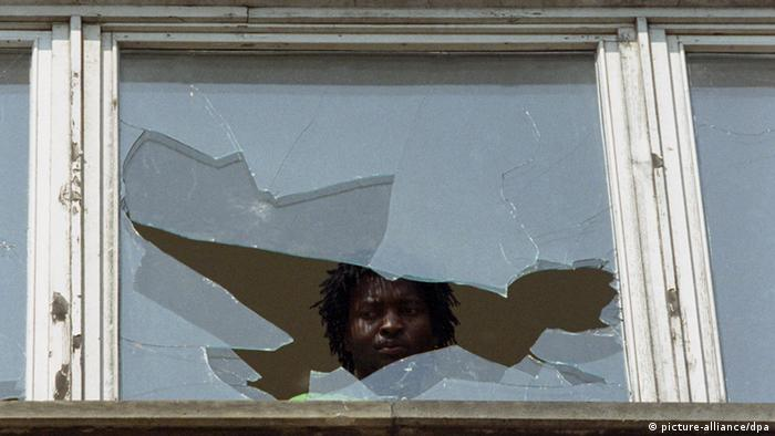 An asylum-seeker looks out a broken window in an archive photo from Hoyerswerda after the 1991 attacks Photo: dpa +++(c) dpa - Bildfunk+++