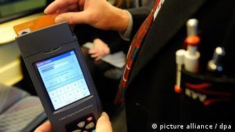 Ein Kontrolleur des Karlsruher Verkehrsverbunds (KVV) überprüft am 18.03.2011 in einer Straßenbahn in Karlsruhe mit einem Handlesegerät die Fahrkarte eines Fahrgastes. Der wirtschaftliche Schaden durch Schwarzfahrer wird durch den KVV auf mehr als vier Millionen Euro im Jahr geschätzt. Foto: Uli Deck dpa/lsw (zu lsw Korr _ Kopfgeldjäger in der Tram - Kontrolleure auf Tour_ vom 29.03.2011) +++(c) dpa - Bildfunk+++