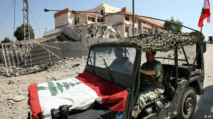 Two Lebanese army soldiers from the 10th infantry brigade drive a jeep with a Lebanese flag covering the hood while patrolling the streets in the southern town of Khiam, Lebanon Friday, Aug. 18, 2006. The Lebanese army reached the country's southern border with Israel for the first time in decades, sending a lone jeep on patrol Friday through Kfar Kila, a battered stronghold of support for Hezbollah militants. (ddp images/AP Photo/Nasser Nasser)