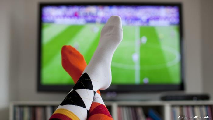 zwei Füße vor einem Bildschirm, auf dem Fußball läuft (Foto: Rolf Vennenbernd dpa/lnw)