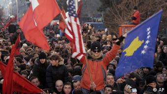 Kosovars celebrate independence in Pristina, Kosovo, waving the new Kosovo flag, right, Sunday, Feb. 17, 2008. Kosovo's parliament declared the disputed territory a nation on Sunday, mounting a historic bid to become an independent and sovereign state backed by the U.S. and key European allies but bitterly contested by Serbia and Russia. (AP Photo/Darko Bandic)