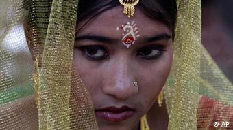 A bride looks on during a mass community marriage
