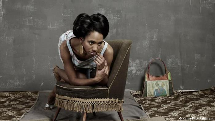 Y'Akoto kniet auf einem Sessel.