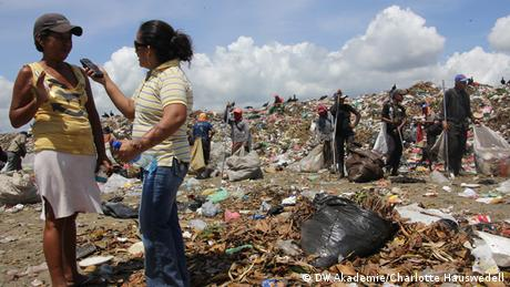 A journalist interviews a woman in a garbage dump in Managua, Nicaragua
