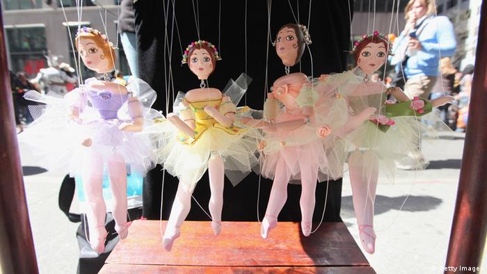 Vier an Fäden hängende Marionetten eines Puppentheaters in Ballerinakleidern