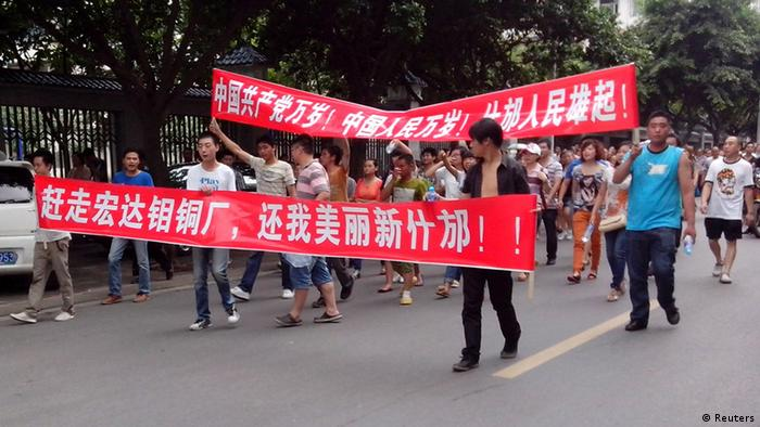 Local residents march with banners during a protest along a street in Shifang, Sichuan province July 3, 2012. Residents in Shifang, a city in southwest China, took to the streets for a third day on Tuesday, demanding the government scrap plans for a copper alloy project they fear will poison them, in the latest unrest spurred by environmental concerns. The Chinese characters on the banners read,