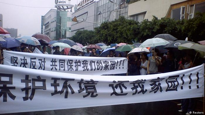 Local residents parade with banners during a protest along a street in Shifang county, Sichuan province in this handout picture taken on July 2, 2012. Shifang, a city in southwest China, has temporarily halted work on a copper alloy project and threatened to punish organisers of a two-day protest against it if they do not give themselves up, in the latest example of unrest spurred by the country's environmental woes. The Chinese characters on the banners read, Protect the environment, Return our homeland!(front) and Stand against it, and stand together to protect our homeland!. Picture taken July 2. REUTERS/Handout (CHINA - Tags: ENVIRONMENT CIVIL UNREST POLITICS) FOR EDITORIAL USE ONLY. NOT FOR SALE FOR MARKETING OR ADVERTISING CAMPAIGNS. CHINA OUT. NO COMMERCIAL OR EDITORIAL SALES IN CHINA