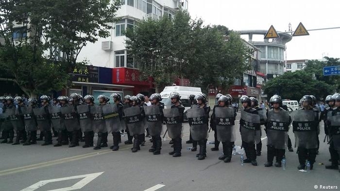 Riot police stand in a line to guard a street during a protest in Shifang, Sichuan province July 3, 2012. Residents in Shifang, a city in southwest China, took to the streets for a third day on Tuesday, demanding the government scrap plans for a copper alloy project they fear will poison them, in the latest unrest spurred by environmental concerns. REUTERS/Stringer (CHINA - Tags: ENVIRONMENT POLITICS CIVIL UNREST) CHINA OUT. NO COMMERCIAL OR EDITORIAL SALES IN CHINA