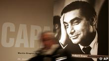 A journalist passes a portrait of photographer Robert Capa during the press preview of a Capa retrospective in Berlin on Friday, Jan. 21, 2005. The 'Martin-Gropius-Bau' museum will show about 300 famous and unknown photographs of Capa from Jan. 22, until April 18, 2005. (ddp images/AP Photo/Markus Schreiber)