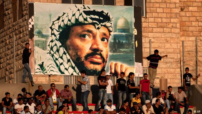 Palestinian soccer fans sit under a large banner showing the late Palestinian leader Yasser Arafat, during a World Cup qualifier game against Thailand in West Bank city of Ramallah, Thursday, July 28, 2011. The Palestinians' hopes of a World Cup place were dashed on Thursday when their team could only draw 2-2 with Thailand, who made it through to the third round of Asian qualifiers with a 3-2 aggregate victory. For the Palestinians, the loss marked a disappointing end to a World Cup qualifying campaign that had become a symbol of nation building.(Foto:Sebastian Scheiner/AP/dapd)