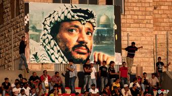 Palestinian soccer fans sit under a large banner showing the late Palestinian leader Yasser Arafat, during a World Cup qualifier game against Thailand in West Bank city of Ramallah, Thursday, July 28, 2011.