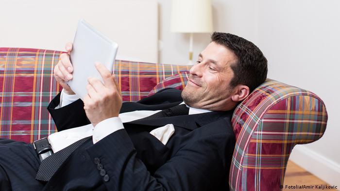 Мужчина в костюме читает сообщения на смартфоне