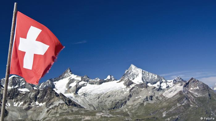 Die Schweizer Flagge weht vor den schneebedeckten Alpen.