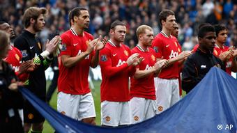 Manchester United players including Wayne Rooney, centre take part in one minute applause for Bolton Wanderers' Fabrice Muamba who suffered a cardiac arrest during his team's FA Cup match against Tottenham before their English Premier League soccer match against Wolverhampton Wanderers at Molineux Stadium, Wolverhampton, England, Sunday, March 18, 2012. (Foto:Jon Super/AP/dapd)