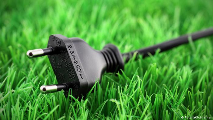 a black electrical plug on green grass