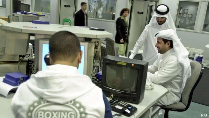 Journalisten des Nachrichensenders Al Jazeera sitzen in der Redaktion in Katar und besprechen sich (Foto: AP)