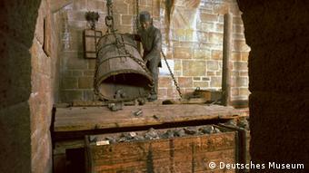 Bildtext: Bergwerk - Hängebank Der Schacht ist in ein Fördertrum und ein Fahrtrum geteilt. Auf der Hängebank, dem obersten Ende des Fördertrums, werden die gefällten Erzkübel abgesetzt und in Wagen gekippt. Das Fahrtrum ist durch Bühnen unterteilt, die mit Leitern (Fahrten) zum Ein- und Ausfahren der Bergleute versehen sind. Frei zur Veröffentlichung nur mit dem Vermerk: Foto: Deutsches Museum