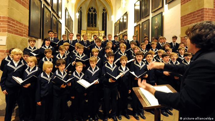 Choir boys lined up in a church and singing (picture-alliance/dpa)