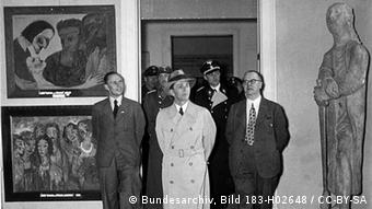In a black-and-white image taken inside a museum in1938, men in drawn overcoats are flanked by a statue on one side and two pieces of art on the other.