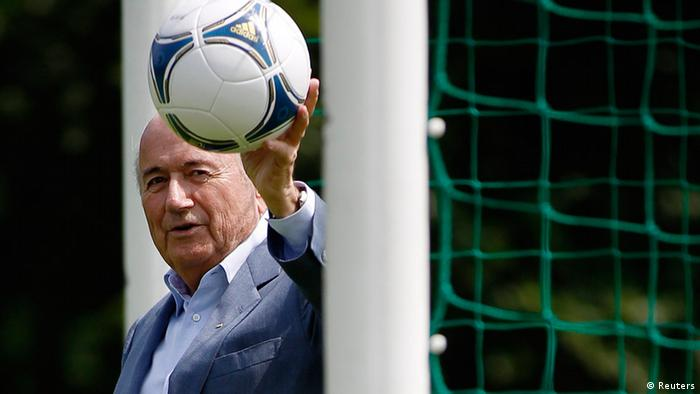International Federation of Football Association (FIFA) President Sepp Blatter poses with a ball at the goal line of a goal, at a local soccer pitch in Zurich July 4, 2012.