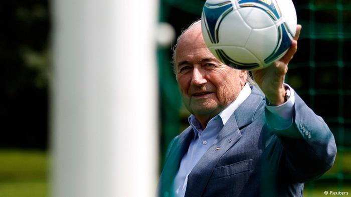International Federation of Football Association (FIFA) President Sepp Blatter poses with a ball on the goal line in a goal of a local soccer pitch in Zurich July 4, 2012. The International Football Association Board (IFAB) will hold a meeting on goal line technology on July 5, at the Home of FIFA in Zurich. REUTERS/Michael Buholzer (SWITZERLAND - Tags: SPORT SOCCER)