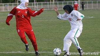 Two women compete for the football in a lower-league game in Berlin, wearing headscarves
