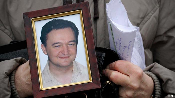 Женщина держит в руках портрет Сергея Магнитского
