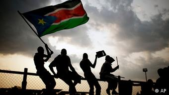 Four people are waving a South Sudanese independence flag