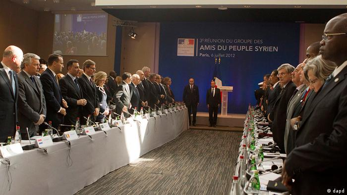 French President Francois Hollande, standing in the center, Foreign Minister Laurent Fabius and delegates stand during a minute of silence for victims of Syrian regime, at the Friends of Syria conference in Paris, Friday, July 6, 2012. Syrian opposition leaders are pressing diplomats at an international conference for a no-fly zone over Syria, but the U.S. and its European and Arab partners are expected to focus on economic sanctions instead. (Foto:Jacques Brinon, Pool/AP/dapd)