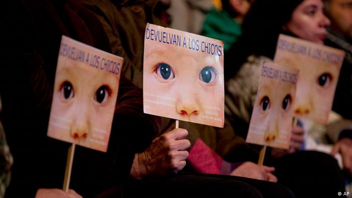 People hold signs that read in Spanish Give the children back outside a court where Argentina's historic stolen babies trial is being held in Buenos Aires on July 5, 2012 (Photo: Natacha Pisarenko)