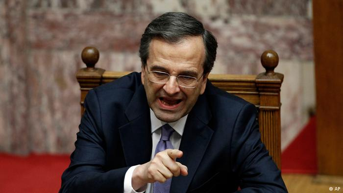 New Greek Prime Minister Antonis Samaras speaks to a colleague during a policy statement session at the parliament in Athens on Friday, July 6, 2012.