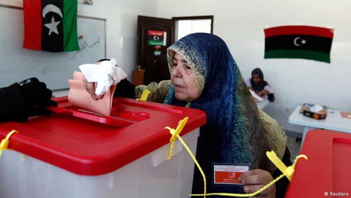 A woman voter drops voting papers inside a ballot box in Sirte July 7, 2012. Libyans queued to vote in their first free national election in 60 years on Saturday, a poll designed to shake off the legacy of Muammar Gaddafi but which risks being hijacked by violence. Libyans will choose a 200-member assembly which will elect a prime minister and cabinet before laying the ground for full parliamentary elections next year under a new constitution. REUTERS/Anis Mili (LIBYA - Tags: POLITICS ELECTIONS)