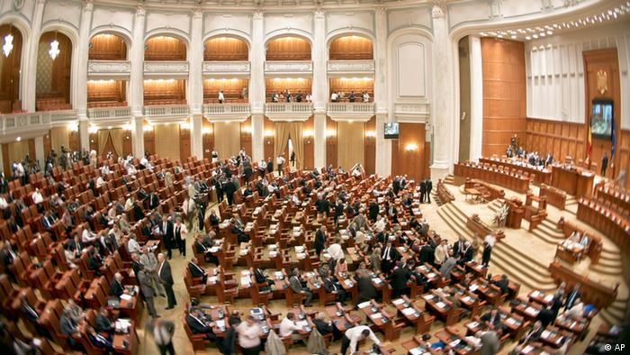 A few hundred people sit in a room wtih curved seating in an ornate governmental setting (Photo:Vadim Ghirda/AP/dapd)