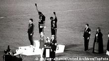 1968 Olympic Games, Mexico City America's gold and bronze medallists Tommie Smith (centre) and John Carlos (right) raise their arms as a 'Black Power' gesture during the Olympic Awards Ceremony. Smith had set a world record of 19.8 seconds in the 200 metre race. Each man wore a black glove on one hand and raised it, with fist clenched as the US flag was raised. Perter Norman from Australia (left) won the silver medal. 16th October 1968. Mexico / Mono Negative