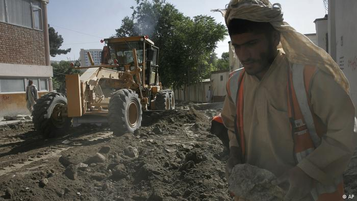 In this Thursday, July 5, 2012 photo, an Afghan laborer carries a stone, as a grader vehicle works on a road to make it ready for asphalt in Kabul, Afghanistan. Afghanistan will seek at least $4 billion from international donors this weekend at a crucial aid conference aimed at propping up the country after most foreign combat troops leave at the end of 2014. (AP Photo/Musadeq Sadeq)