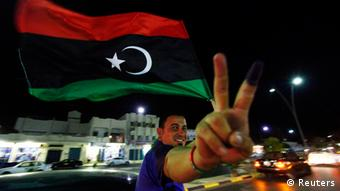 A man, with an inked finger, flashes the victory sign as he celebrates with the new Libyan flag at the end of voting day in Sirte July 7, 2012. Libyans defied violence and boycott calls to rush to the polls in their first free national election in 60 years on Saturday, parting with the legacy of Muammar Gaddafi's dictatorship. REUTERS/Anis Mili (LIBYA - Tags: POLITICS ELECTIONS TPX IMAGES OF THE DAY)
