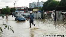 epa03299825 A man runs in a flooded street in Krymsk, Krasnodar region, Russia, 07 July 2012. Media reports on 07 July 2012 state that at least 105 people were reported dead after flash floods hit the southern Russian, Krasnodar region with the death toll still rising. EPA/TIMUR GROMOV +++(c) dpa - Bildfunk+++