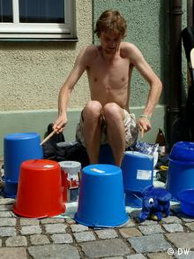 A street musician performs on upturned buckets