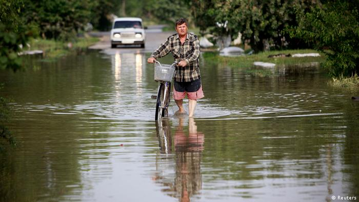 A local resident pulls his bicycle along a flooded street in the town of Krymsk in Krasnodar region, southern Russia, July 8, 2012. Russian President Vladimir Putin ordered investigators to find out if enough was done to prevent 144 people being killed in floods in southern Russia after flying to the region to deal with the first big disaster of his new presidency. REUTERS/Eduard Korniyenko (RUSSIA - Tags: DISASTER ENVIRONMENT POLITICS)