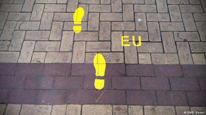 A picture of yellow footsteps on a Brussels street with the letters EU to the right of them.