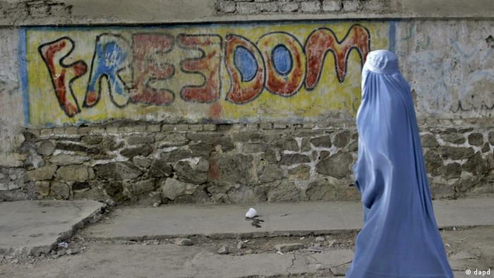 An Afghan woman clad in a burqa walks past a graffiti painted wall, in Herat, west of Kabul, Afghanistan on Thursday, May 13, 2010. (AP Photo/Reza Shirmohammadi)