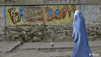 An Afghan woman clad in a burqa walks past a graffiti painted wall, in Herat