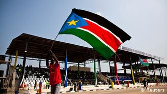 A man waves the national flag of South Sudan during celebrations to mark the country's first anniversary of its independence in Juba, July 9, 2012. South Sudanese celebrating their nation's first birthday on Monday will bask in the pride of their hard-won political freedom, but many may ask when they will enjoy the material benefits promised by the government of former rebels. REUTERS/Adriane Ohanesian (SOUTH SUDAN - Tags: SOCIETY ANNIVERSARY POLITICS)