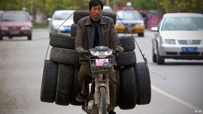 A man rides on an electric bike loaded with used tires in Beijing Tuesday, April 26, 2011. (AP Photo/Alexander F. Yuan)