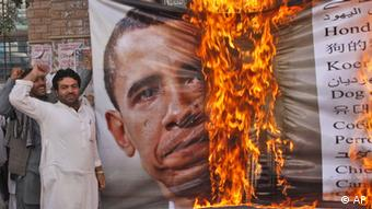Supporters of Pakistan's religious parties burn a banner with President Barack Obama's image on it