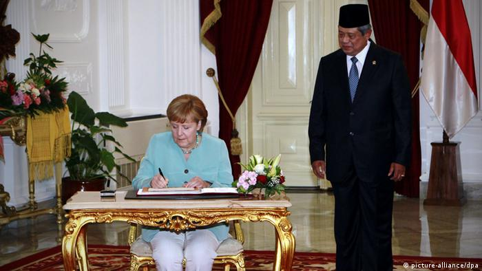 epa03302325 German Chancellor Angela Merkel (L) signs the guest book as Indonesia's President Susilo Bambang Yudhoyono looks on during her arrival at the Presidential Palace in Jakarta, Indonesia, 10 July 2012. Reports state Merkel will seek to strengthen trade ties with Indonesia during her first official visit to South East Asia s biggest economy as she tries to offset weak demand from Germany s eurozone partners. Indonesia is Germany's fourth biggest trading partner in the 10-member Association of Southeast Asian Nations (ASEAN) which has a combined population of 575 million people about 8 per cent of the world population. EPA/MAST IRHAM