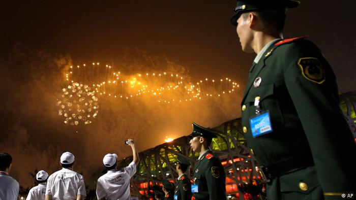 Police and volunteers watch the Olympic rings made from fireworks during the opening ceremony in the National Stadium at the Beijing 2008 Olympics in Beijing, Friday, Aug. 8, 2008. (AP Photo/Natacha Pisarenko)