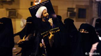 A protester holds up a picture of Sheikh Nimr al-Nimr during a rally at the coastal town of Qatif, against Sheikh Nimr's arrest July 8, 2012.