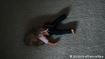 Eine Puppe liegt in einem Kinderzimmer auf dem Teppich (Foto: pa/dpa)