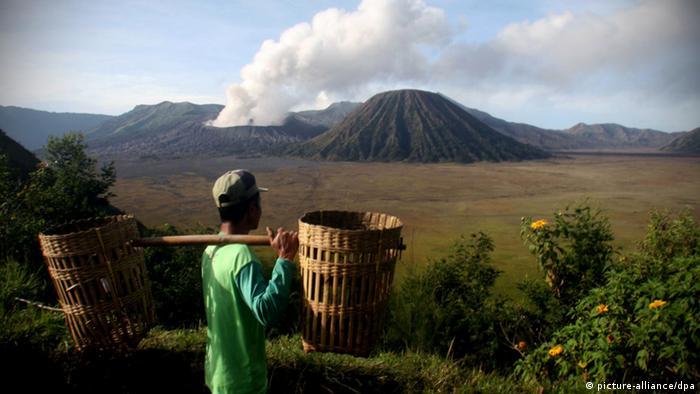 A farmer watches Mount Bromo spews hot clouds from Ngadisari Village, Probolinggo, Indonesia